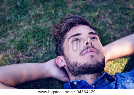 Young man lying down in the park on a summer day