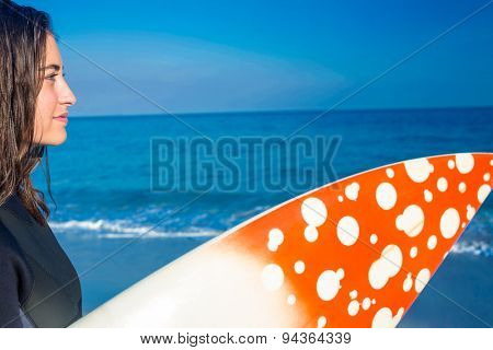 Woman in wetsuit with a surfboard on a sunny day at the beach
