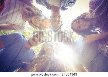 Happy friends huddling in circle in the park on a sunny day