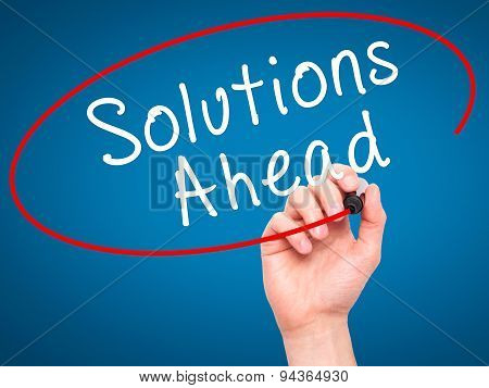 Man Hand writing Solutions Ahead with black marker on visual screen.