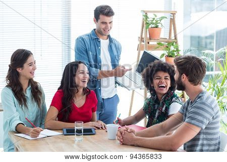 Young businessman showing his laptop to colleagues at office