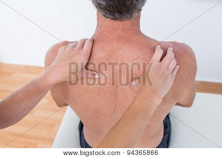 Doctor examining his patient shoulder in medical office