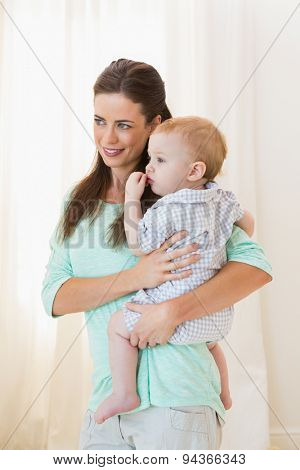 Happy mother holding baby boy at home