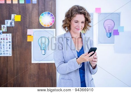 Creative businesswoman using her smartphone in office