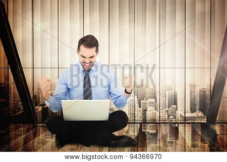 Businessman sitting with his laptop cheering against window overlooking citty