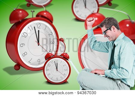Businessman wearing glasses and using laptop against green vignette