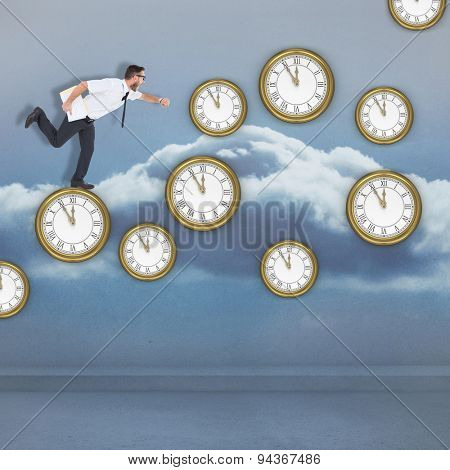 Geeky young businessman running late against clouds in a room
