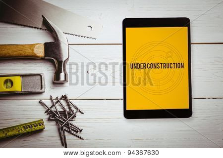 The word under construction and tablet pc against blueprint
