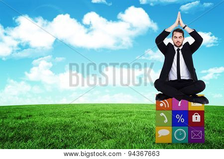 Businessman sitting in lotus pose with hands together against blue sky over green field
