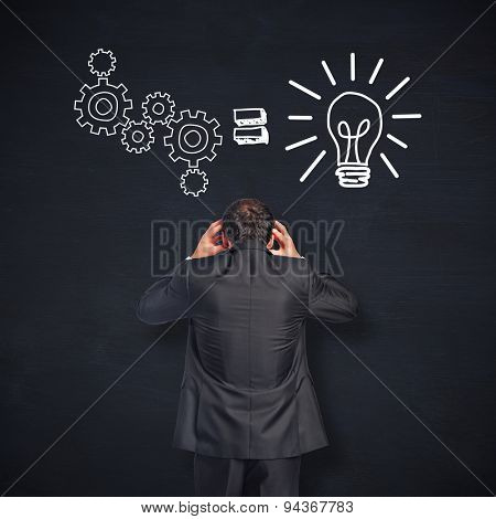 Stressed businessman with hands on head against blackboard