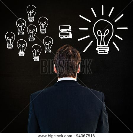 Rear view of businessman standing against black