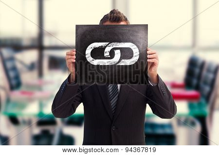 Businessman showing board against empty corporate meeting room