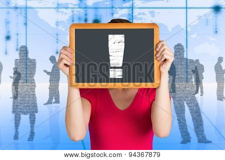 Woman covering face with chalkboard against black silhouettes in blue room