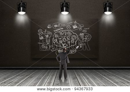 Businessman standing back to the camera with hand on head against blackboard