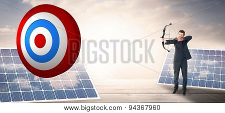 Businessman shooting a bow and arrow against solar panels on floorboards in the sky