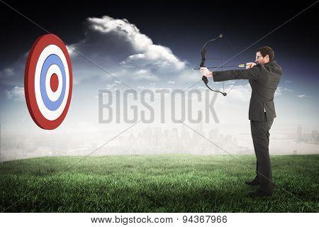 Businessman shooting a bow and arrow against blue sky over city
