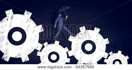 Businessman walking and holding umbrella against black