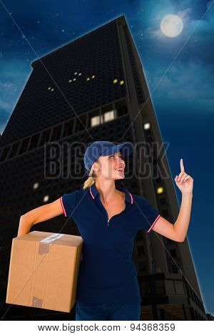 Happy delivery woman holding cardboard box and pointing up against city at night