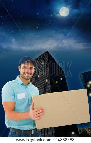 Courier man carrying cardboard box against city at night