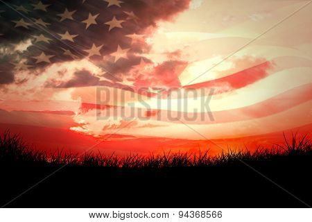 Digitally generated american flag rippling against red sky over grass