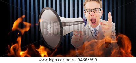 Geeky businessman shouting through megaphone against dark grey room