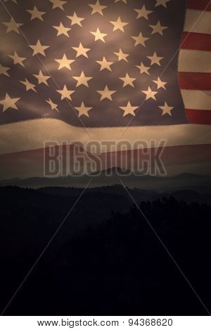 United states of america flag against trees and mountain range against cloudscape