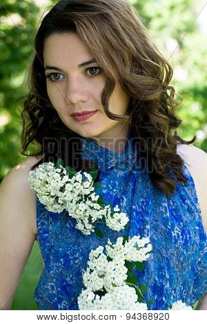 The Girl In A Blue Dress Holding A Branch With White Flowers