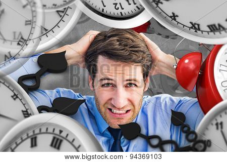 Stressed businessman with hands on head against grey background