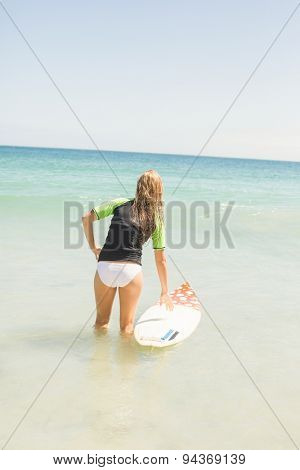 Wear view of pretty blonde preparing to surf at the beach