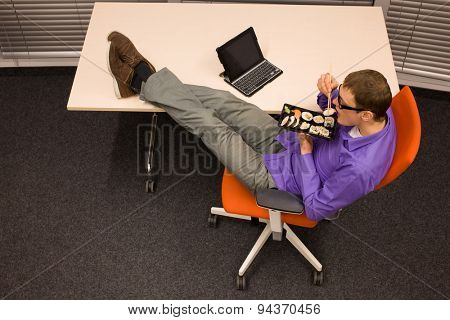 man sitting at with legs on the desk, heaving break in work eating sushi with chopsticks in office