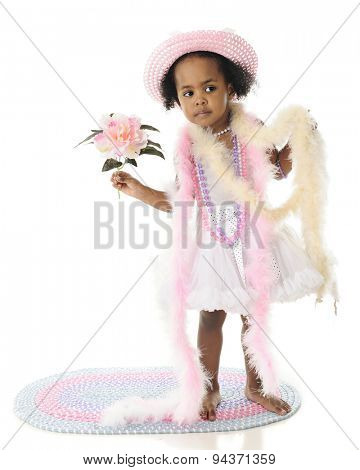 An adorable 2 year old looking in the distance as she stands in her petticoat, beads and boats.  He holds a large flower in her hand.  On a white background.