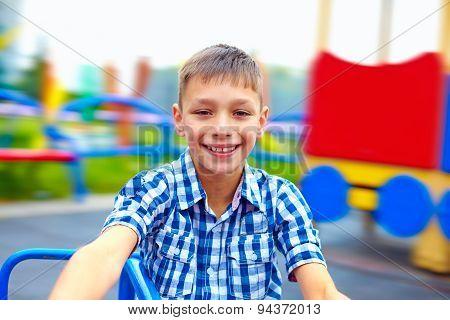 Joyful Teenage Boy Having Fun On Roundabout, Playground