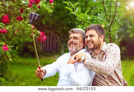 Like Father Like Son. Family Makes Selfie On Smartphone