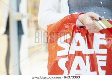 Close Up Of Shopper Holding Credit Card And Bag In Mall