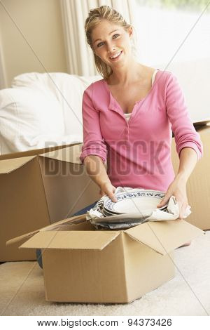 Young Woman Moving Into New Home Unpacking Boxes