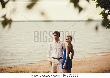 Young Couple Standing On The Shore Of The Lake