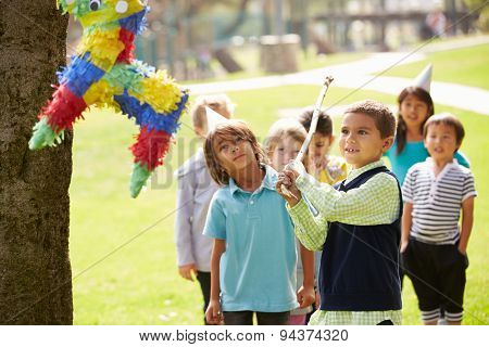 Children Hitting Pinata At Birthday Party