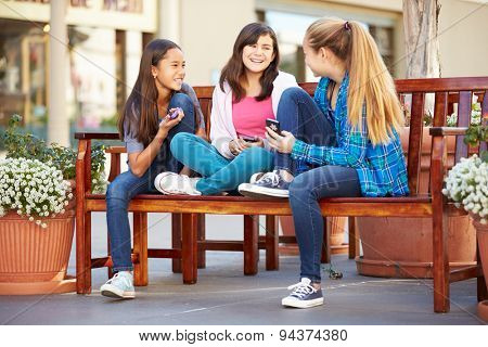 Group Of Girls Sitting In Mall Using Mobile Phones