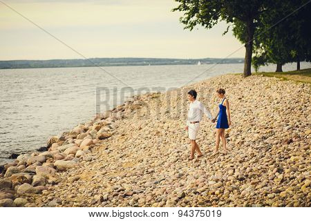 Young Couple Walking Along The Beach At Sunset