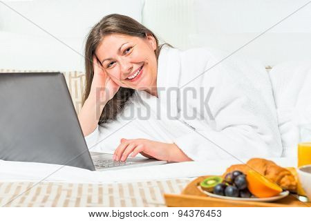 Smiling Woman In Bed With A Laptop And Breakfast Tray