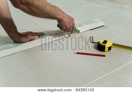 Man Cuts Off A Piece Of Drywall