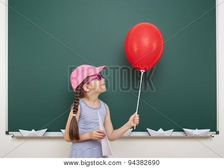 Schoolgirl with red balloon near the school board