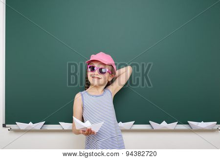 Schoolgirl with origami ship near the school board