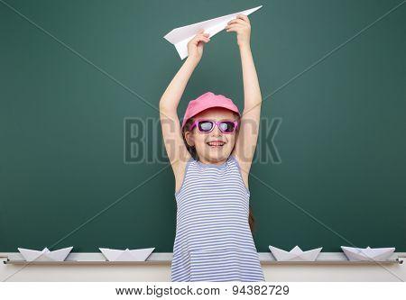 Schoolgirl with origami plane near school board