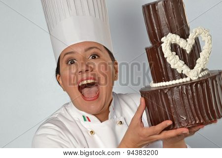 Happy pastry cook woman holding a big chocolate cake. Cake design woman.