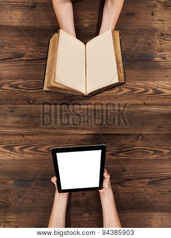 Woman hands holding blank old book and modern tablet device on wooden planks. Classical and modern reading concept