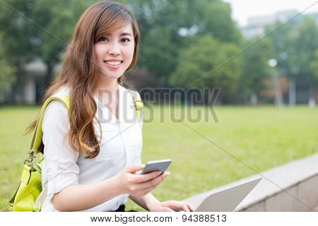 Asian beautiful female studen using mobile phone in campus