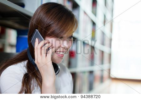 Asian beautiful female student using laptop and mobile phone in library