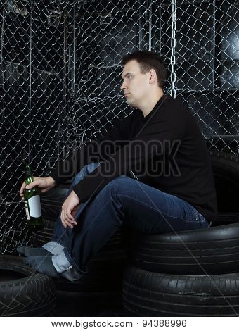 Portrait Of Sad Man With Bottle Sitting On Tires In Room With Net