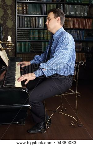 Young Man Plays Piano In Room With Bookshelves And Brown Wallpapers
